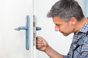 Carpenter Fixing Lock In Door With Screwdriver